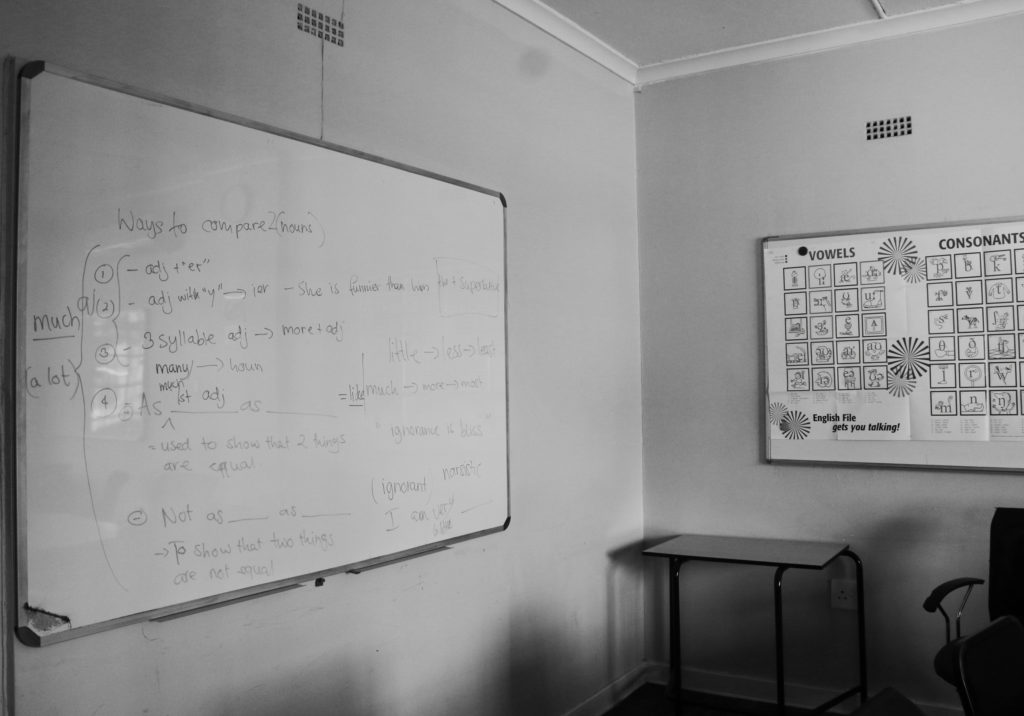 If these walls could talk: a white board with the lesson of the day and a poster with vowles.